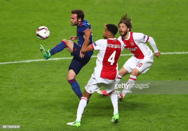 Juan Mata of Manchester United controls the ball while under pressure from Jairo Riedewald of Ajax and Lasse Schone of Ajax during the UEFA Europa...
