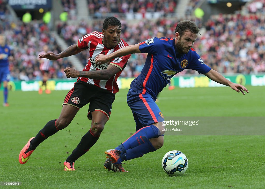 Juan Mata of Manchester United in action with Patrick van Aanholt of Sunderland during the Barclays Premier League match between Sunderland and Manchester United at Stadium of Light on August 24, 2014 in Sunderland, England.