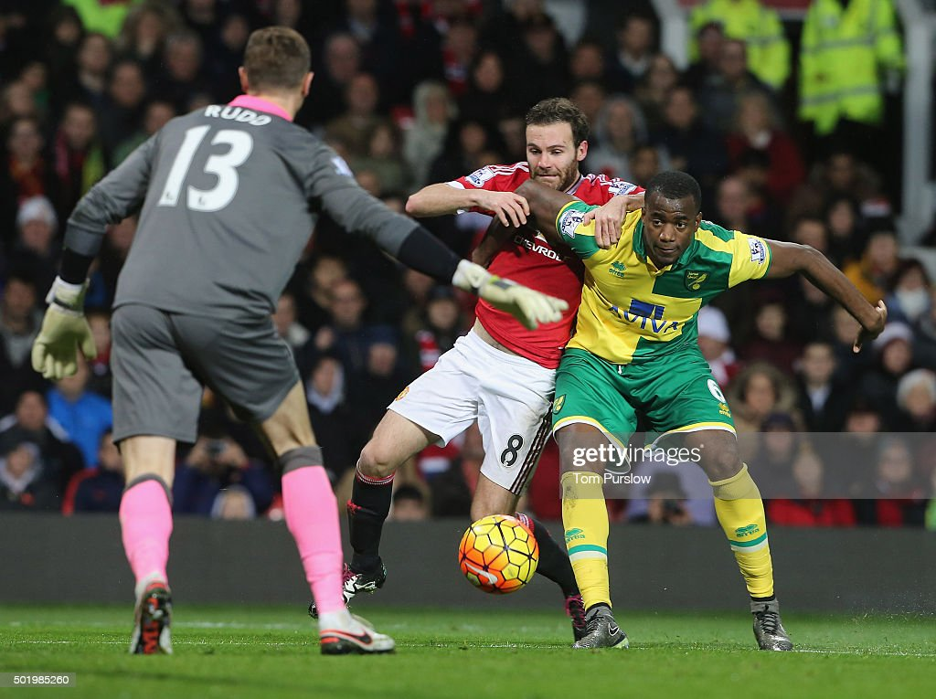 Juan Mata of Manchester United in action with Sebastien Bassong of Norwich City during the Barclays Premier League match between Manchester United...