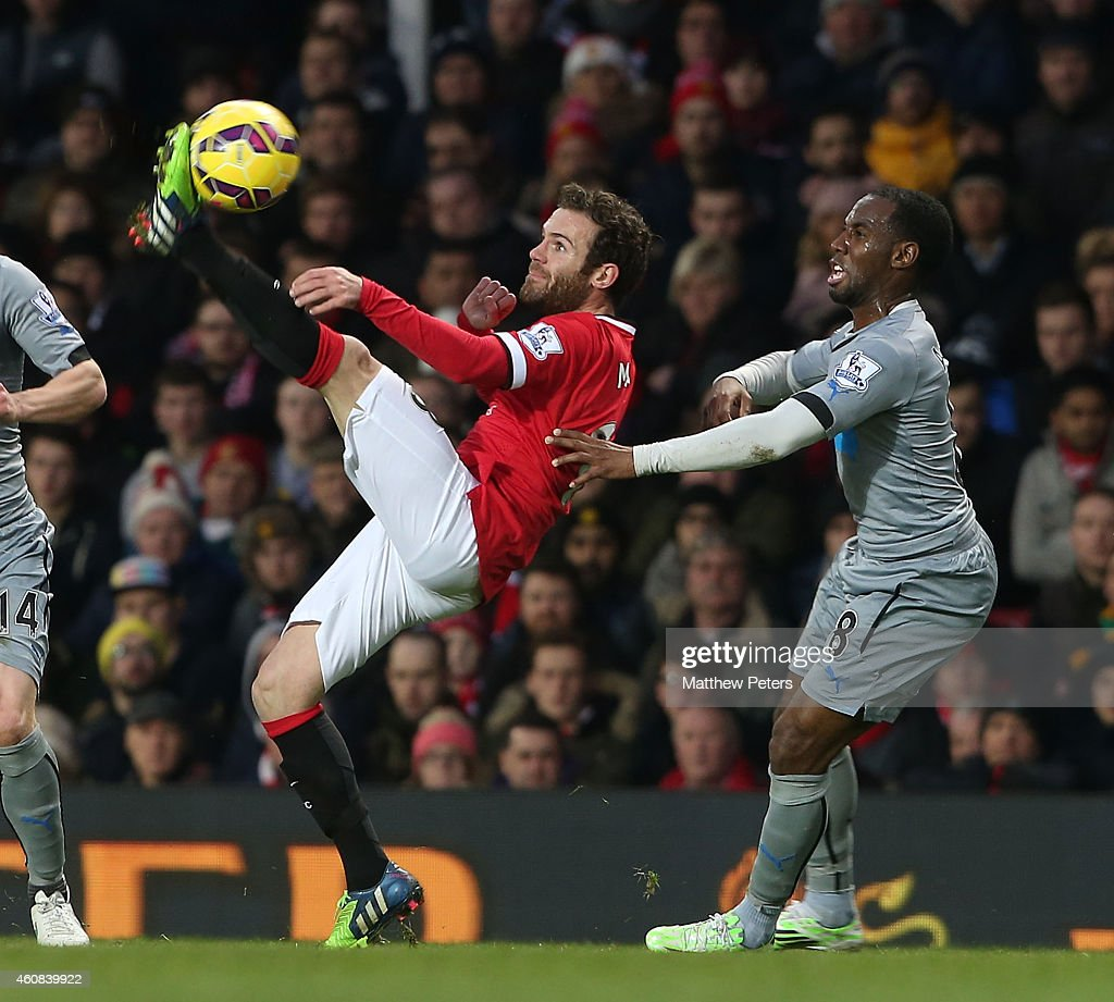 Juan Mata of Manchester United in action with Vurnon Anita of Newcastle United during the Barclays Premier League match between Manchester United and Newcastle United at Old Trafford on December 26, 2014 in Manchester, England.