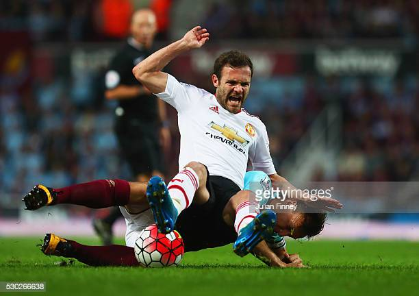 Juan Mata of Manchester United is challenged by Mark Noble of West Ham United during the Barclays Premier League match between West Ham United and...