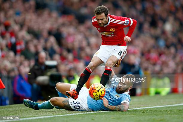 Juan Mata of Manchester United is tackled by Nicolas Otamendi of Manchester City during the Barclays Premier League match between Manchester United...