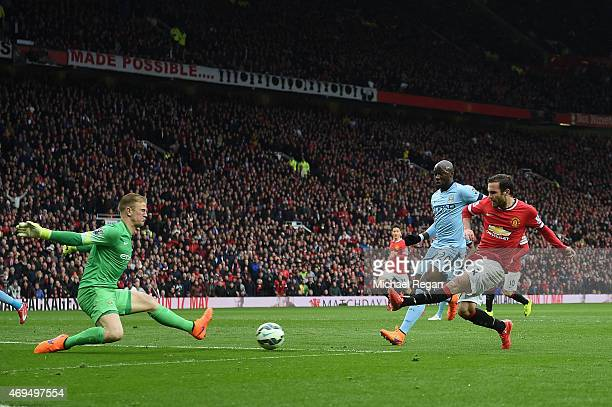 Juan Mata of Manchester United shoots past Joe Hart of Manchester City to score their third goal during the Barclays Premier League match between...
