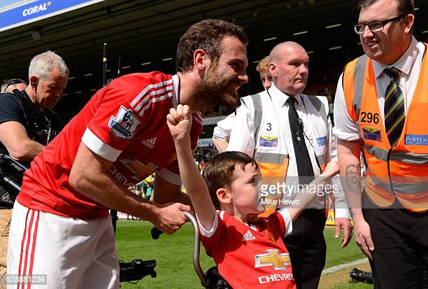Juan Mata of Manchester United with a fan celebrate their win after the Barclays Premier League match between Norwich City and Manchester United at...