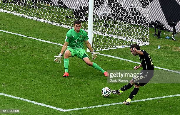 Juan Mata of Spain scores his team's third goal past Mathew Ryan of Australia during the 2014 FIFA World Cup Brazil Group B match between Australia...