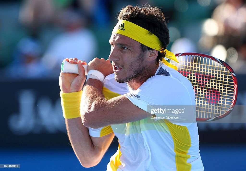 Juan Monaco of Argentina plays a backhand in his first round match against Andrey Kuznetsov of Russia during day one of the 2013 Australian Open at Melbourne Park on January 14, 2013 in Melbourne, Australia.