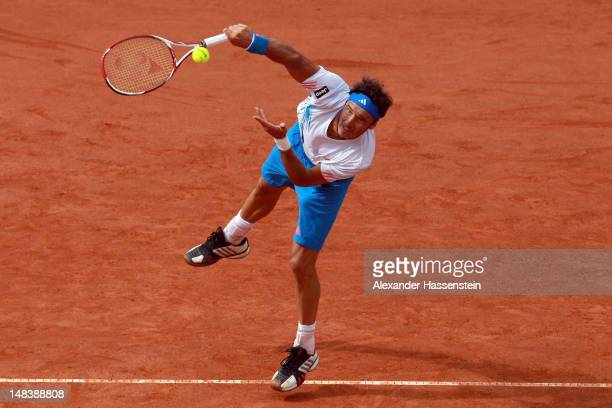 Juan Monaco of Argentinia serves during his finale match against Janko Tipsarevic of Serbia during day 6 of Mercedes Cup 2012 at the TC Weissenhof on...