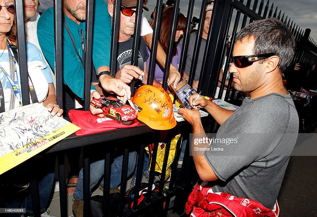 Juan Montoya, driver of the #42 Target Chevrolet, signs autographs during qualifying for the NASCAR Sprint Cup Series Pocono 400 presented by #NASCAR at Pocono Raceway on June 9, 2012 in Long Pond, Pennsylvania.