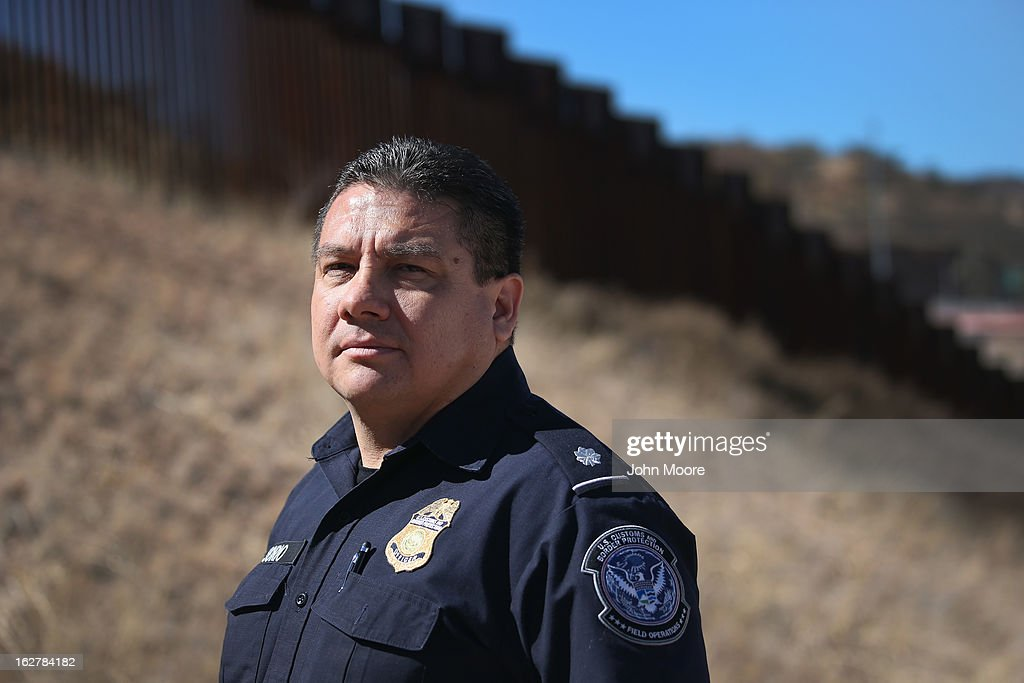 Juan Osorio from the U.S. Office of Field Operations (OFO), stands near the U.S.-Mexico border fence on February 26, 2013 in Nogales, Arizona. Some 15,000 people cross between Mexico and the U.S. each day in Nogales, Arizona's busiest border crossing.