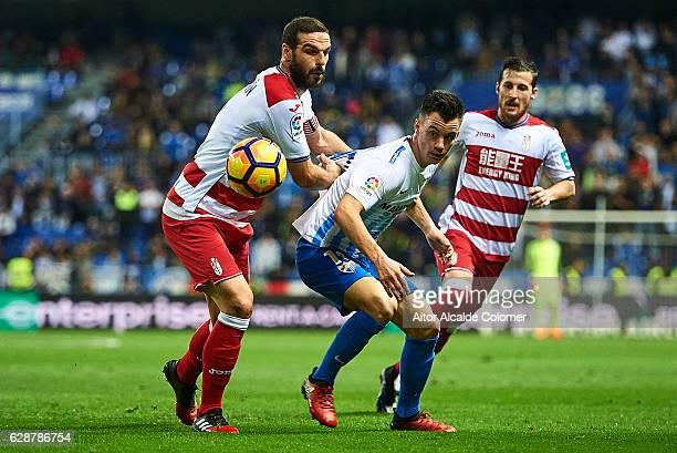 Juan Pablo Anor 'Juanpi' of Malaga CF competes for the ball with David Rodriguez Lomban of Granada CF during La Liga match between Malaga CF and...