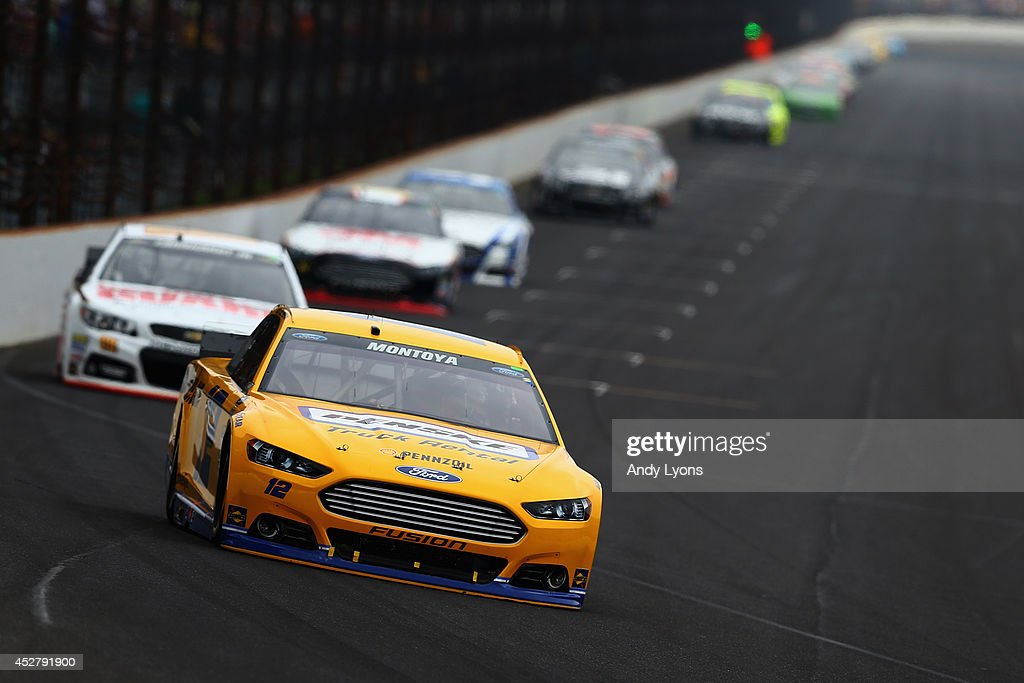 Juan Pablo Montoya, driver of the #12 Penske Truck Rental Ford, leads a pack of cars during the NASCAR Sprint Cup Series Crown Royal Presents The John Wayne Walding 400 at the Brickyard Indianapolis Motor Speedway on July 27, 2014 in Indianapolis, Indiana.