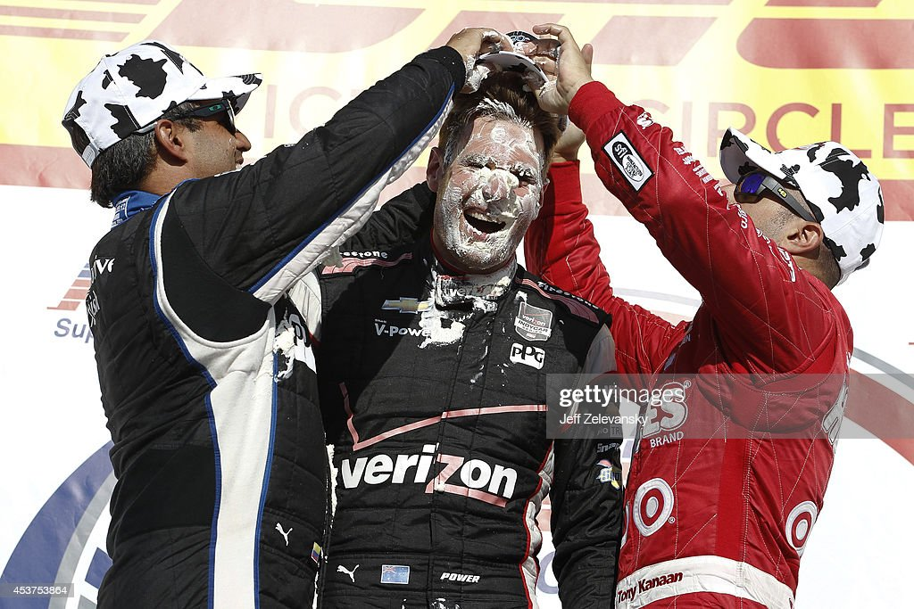 <a gi-track='captionPersonalityLinkClicked' href=/galleries/search?phrase=Juan+Pablo+Montoya&family=editorial&specificpeople=202004 ng-click='$event.stopPropagation()'>Juan Pablo Montoya</a> of Colombia, driver of the #2 PPG Team Penske Chevrolet and <a gi-track='captionPersonalityLinkClicked' href=/galleries/search?phrase=Tony+Kanaan&family=editorial&specificpeople=171962 ng-click='$event.stopPropagation()'>Tony Kanaan</a> of Brazil, driver of the #10 Huggies Target Chip Ganassi Racing Chevrolet, mash cream puffs into the face of Will Power of Australia, driver of the #12 Verizon Team Penske Chevrolet, as they celebrate in victory lane after winning the ABC Supply Wisconsin 250 at The Milwaukee Mile on August 17, 2014 in West Allis, Wisconsin.
