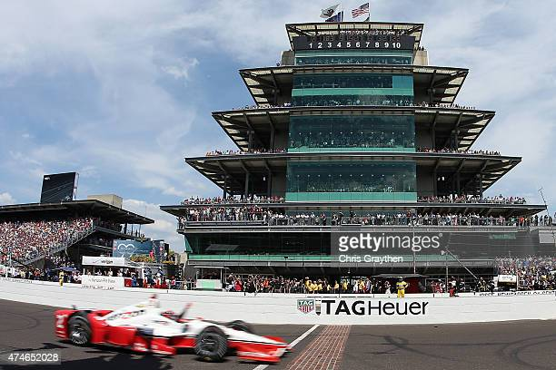 Juan Pablo Montoya of Colombia driver of the Team Penske Chevrolet Dallara celebrates as he crosses the finish line to win the 99th running of the...
