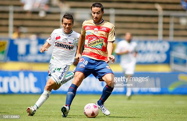 Juan Pablo Rodriguez of Santos fights for the ball with Luis Gabriel Rey of Morelia during a match as part of the Apertura 2010 at Morelos Stadium on...