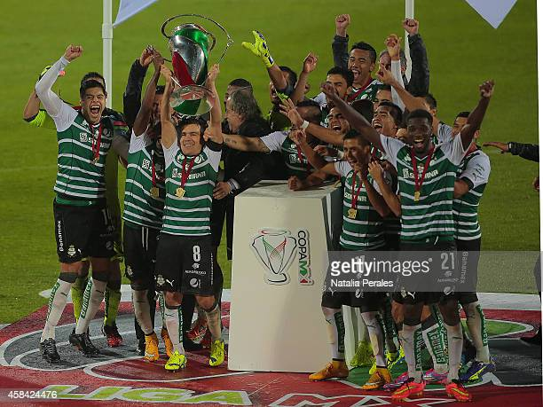 Juan Pablo Rodriguez rises the Champions trophy as his teammates celebrate after a Final match between Santos Laguna and Puebla as part of Copa MX...