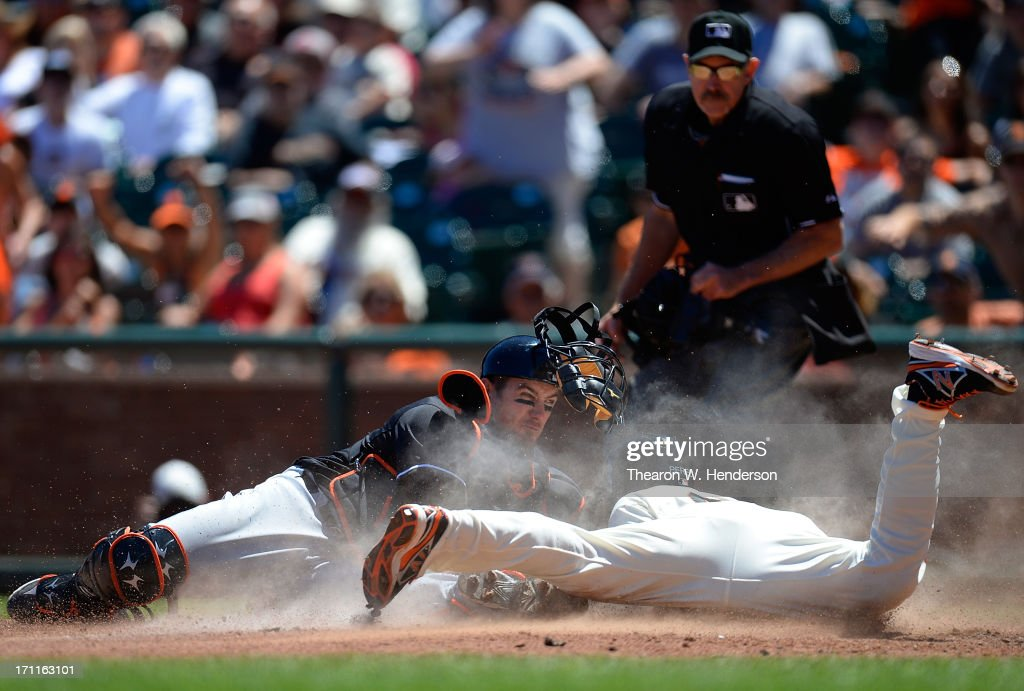 Juan Perez #2 of the San Francisco Giants attempting to score on a squeeze play is tagged out by Jeff Mathis #6 of the Miami Marlins in the fifth inning at AT&T Park on June 22, 2013 in San Francisco, California.