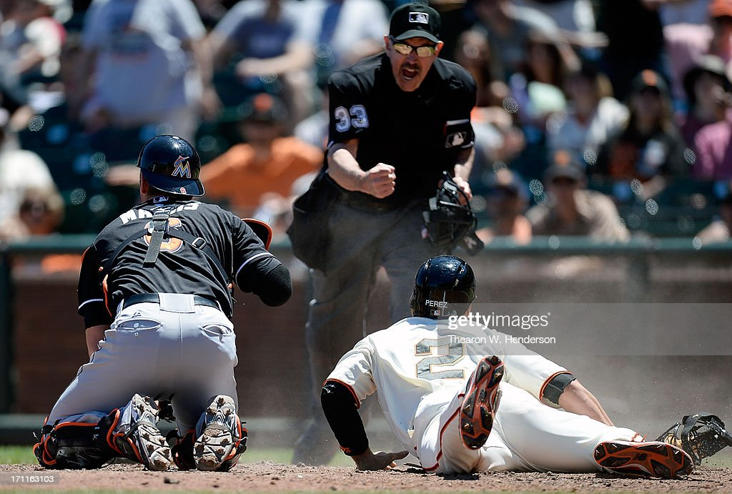 Juan Perez #2 of the San Francisco Giants attempting to score on a squeeze play is tagged by Jeff Mathis #6 of the Miami Marlins and called out by home plate umpire Mike Winters #33 in the fifth inning at AT&T Park on June 22, 2013 in San Francisco, California.