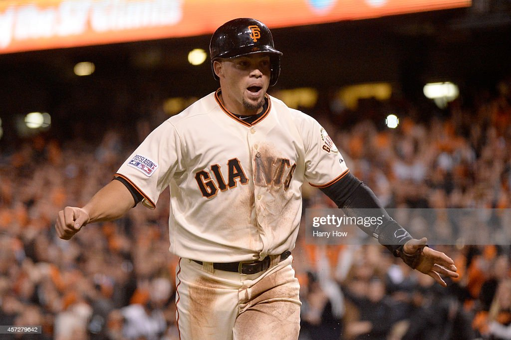 Juan Perez #2 of the San Francisco Giants celebrates after scoring in the sixth inning against the St. Louis Cardinals during Game Four of the National League Championship Series at AT&T Park on October 15, 2014 in San Francisco, California.