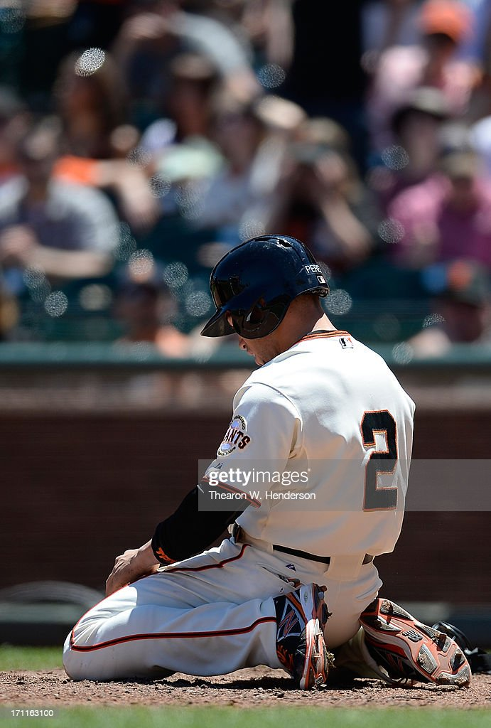 Juan Perez #2 of the San Francisco Giants sits on his knees after attempting to score on a squeeze play and was called out in the fifth inning against the Miami Marlins at AT&T Park on June 22, 2013 in San Francisco, California.