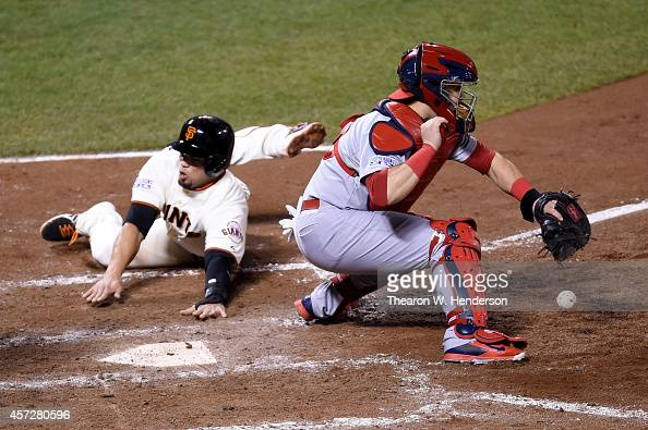 Juan Perez of the San Francisco Giants slides home safely as catcher Tony Cruz of the St Louis Cardinals is unable to catch the ball in the sixth...