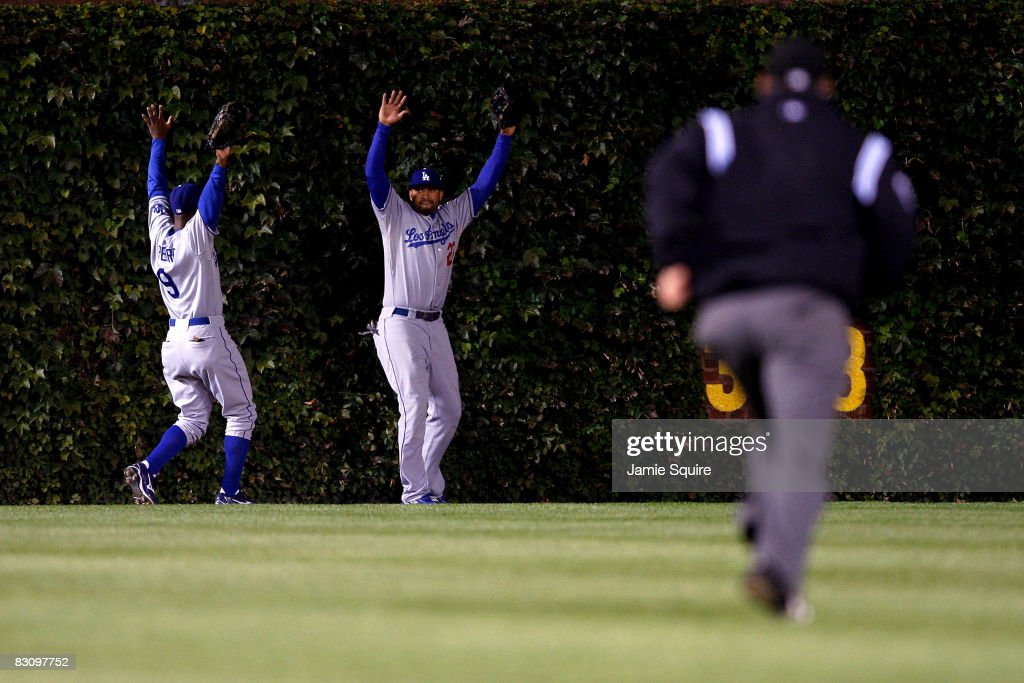 Juan Pierre #9 and Matt Kemp #27 of the Los Angeles Dodgers raise their arms towards the umpire as they lost the ball in the ivy on a ground rule double hit by Derrek Lee #25 of the Chicago Cubs in Game Two of the NLDS during the 2008 MLB Playoffs at Wrigley Field on October 2, 2008 in Chicago, Illinois. The Dodgers won 10-3.