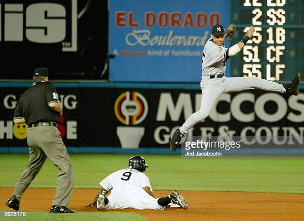 Juan Pierre of the Florida Marlins is safe at second base as Derek Jeter of the New York Yankees leaps for the throw in the first inning of Game 3 of...