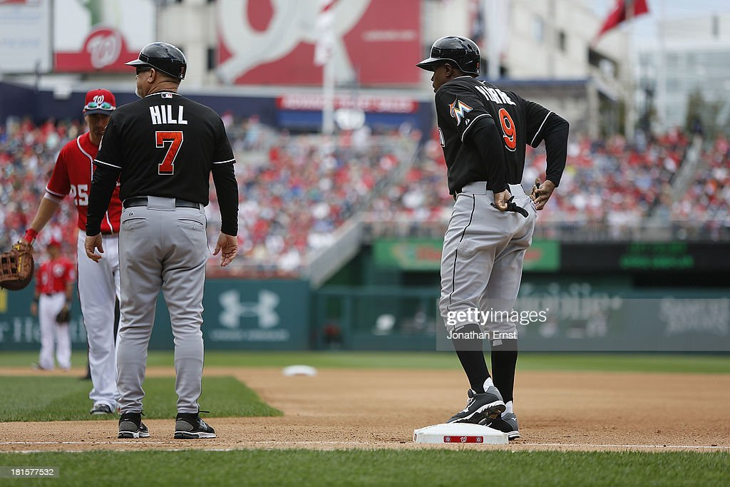<a gi-track='captionPersonalityLinkClicked' href=/galleries/search?phrase=Juan+Pierre&family=editorial&specificpeople=202961 ng-click='$event.stopPropagation()'>Juan Pierre</a> #9 (R) of the Miami Marlins stands at first base after his 2,216th career hit, moving him past Joe DiMaggio for 174th all-time, during the seventh inning against the Washington Nationals in game 1 of their day-night doubleheader at Nationals Park on September 22, 2013 in Washington, DC. Also pictured is first base coach Perry Hill #7 of the Miami Marlins. The Marlins won the game, 4-2.