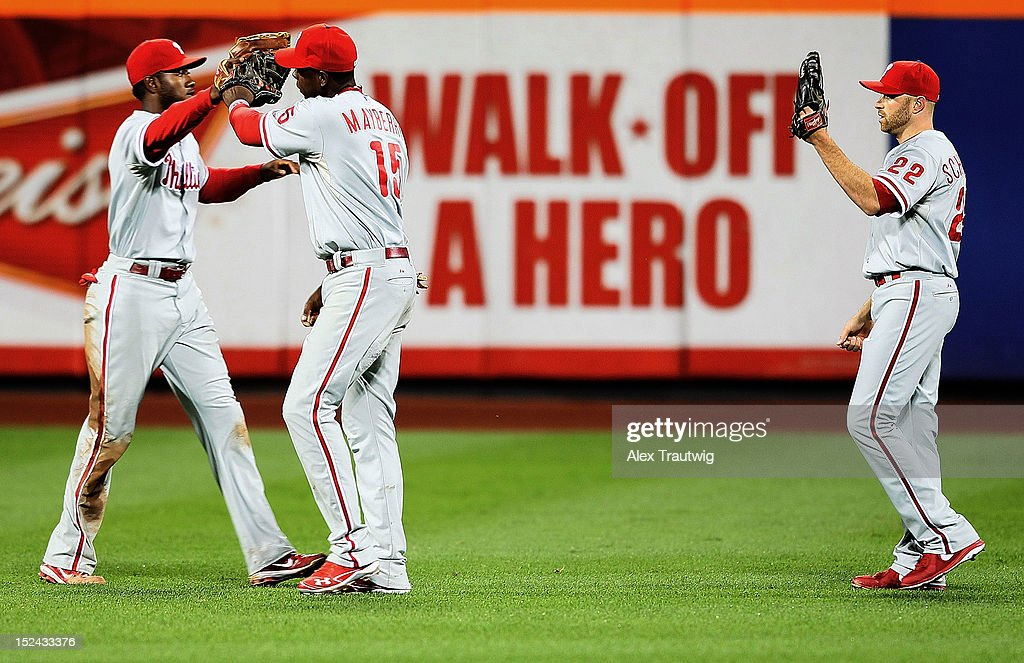 Juan Pierre #10 of the Philadelphia Phillies celebrateas with teammates John Mayberry Jr. #15 and Nate Schierholtz #22 after defeating the New York Mets 16-1 at Citi Field on September 20, 2012 in the Flushing neighborhood of the Queens borough of New York City.