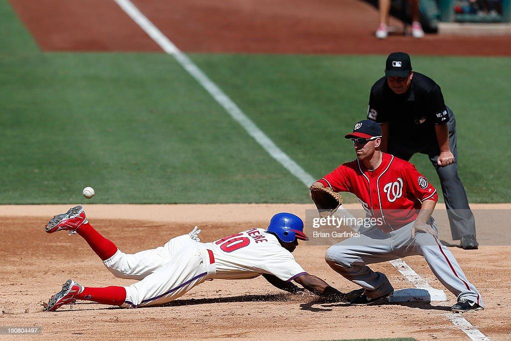 <a gi-track='captionPersonalityLinkClicked' href=/galleries/search?phrase=Juan+Pierre&family=editorial&specificpeople=202961 ng-click='$event.stopPropagation()'>Juan Pierre</a> #10 of the Philadelphia Phillies dives back to first and beats the throw to <a gi-track='captionPersonalityLinkClicked' href=/galleries/search?phrase=Adam+LaRoche&family=editorial&specificpeople=216533 ng-click='$event.stopPropagation()'>Adam LaRoche</a> #25 of the Washington Nationals in the fifth inning of the game at Citizens Bank Park on August 26, 2012 in Philadelphia, Pennsylvania.