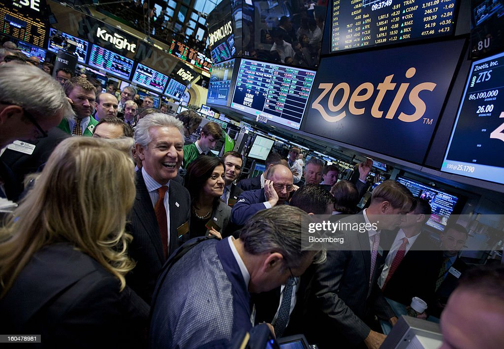 Juan Ramon Alaix, chief executive officer of Zoetis Inc., center left, smiles after ringing the opening bell at the New York Stock Exchange (NYSE) in New York, U.S., on Friday, Feb. 1, 2013. Zoetis Inc., the animal-health company owned by Pfizer Inc., surged as much as 22 percent in its debut after raising $2.24 billion in its initial public offering, pricing the shares above the proposed price range. Photographer: Jin Lee/Bloomberg via Getty Images
