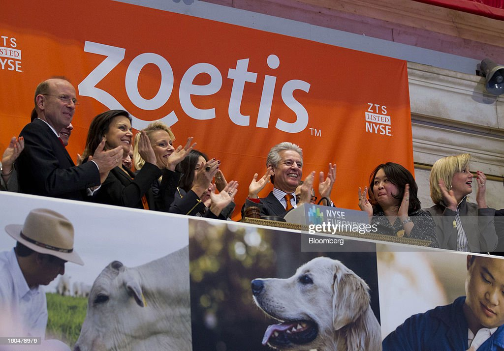 Juan Ramon Alaix, chief executive officer of Zoetis, third left, applauds while ringing the opening bell on the floor of the New York Stock Exchange (NYSE) in New York, U.S., on Friday, Feb. 1, 2013. Zoetis Inc., the animal-health company owned by Pfizer Inc., surged as much as 22 percent in its debut after raising $2.24 billion in its initial public offering, pricing the shares above the proposed price range. Photographer: Jin Lee/Bloomberg via Getty Images