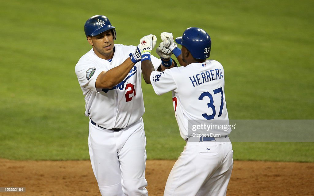 Juan Rivera #21 and Elian Herrera #37 of the Los Angeles Dodgers celebrate after both score on Rivera's two run home run in the ninth inning against the San Francisco Giants on October 3, 2012 at Dodger Stadium in Los Angeles, California. The Dodgers won 5-1.