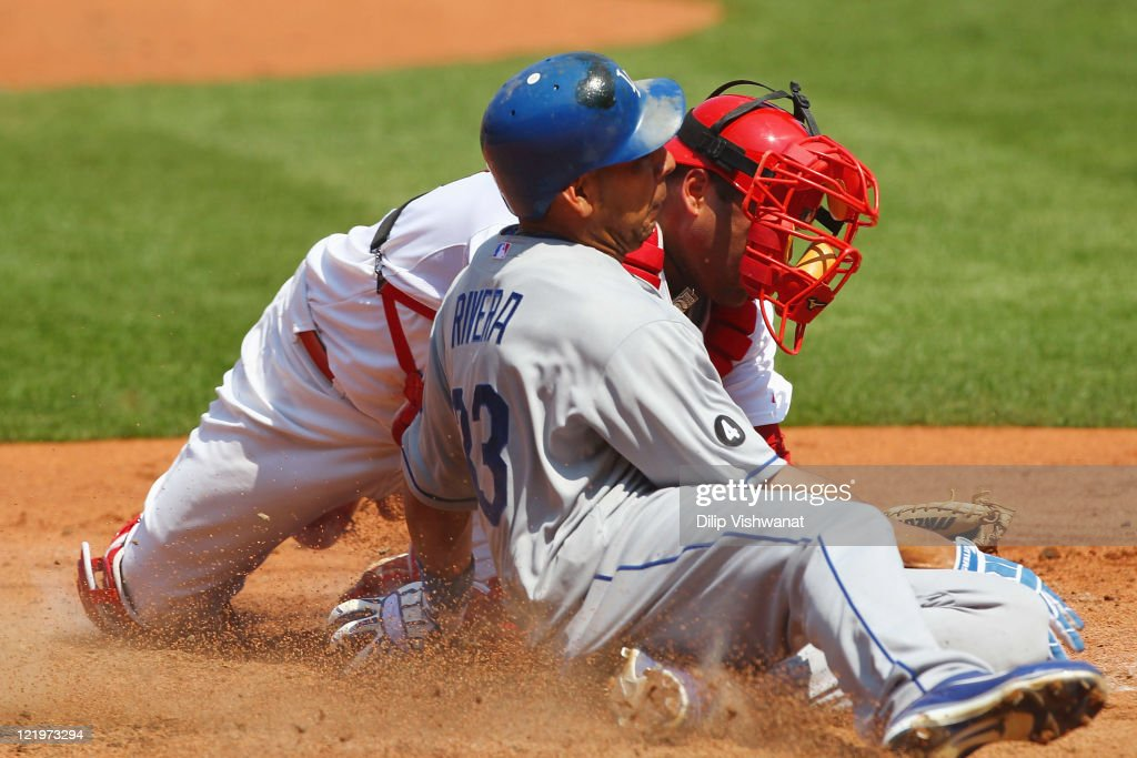 Juan Rivera #33 of the Los Angeles Dodgers scores a run against <a gi-track='captionPersonalityLinkClicked' href=/galleries/search?phrase=Gerald+Laird&family=editorial&specificpeople=228949 ng-click='$event.stopPropagation()'>Gerald Laird</a> #13 of the St. Louis Cardinals at Busch Stadium on August 24, 2011 in St. Louis, Missouri.