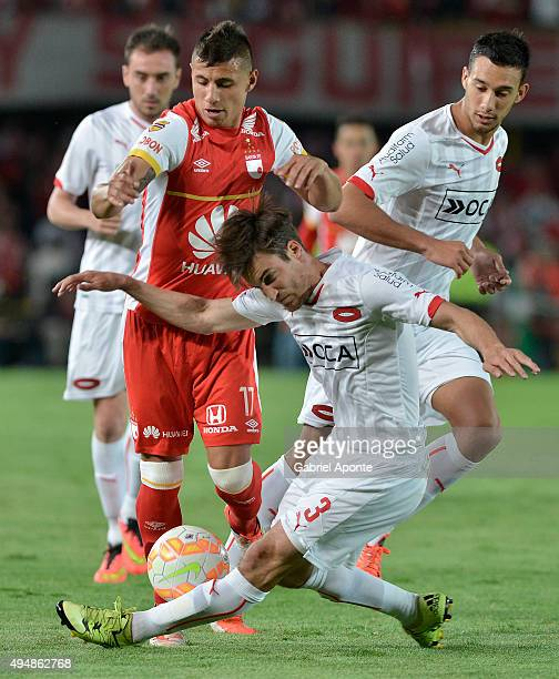 Juan Roa of Santa Fe struggles for the ball with Nicolas Tagliafico of Independiente during a second leg Quarter Final match between Independiente...