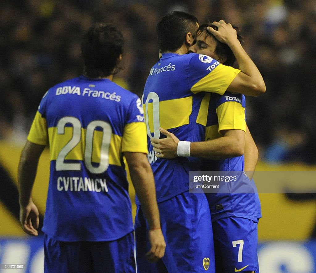 <a gi-track='captionPersonalityLinkClicked' href=/galleries/search?phrase=Juan+Roman+Riquelme&family=editorial&specificpeople=243174 ng-click='$event.stopPropagation()'>Juan Roman Riquelme</a> hugs Pablo Mouche, author of the goal, while <a gi-track='captionPersonalityLinkClicked' href=/galleries/search?phrase=Dario+Cvitanich&family=editorial&specificpeople=4206841 ng-click='$event.stopPropagation()'>Dario Cvitanich</a> walks to join them during a match as part of the Santander Libertadores Cup at Alberto J. Armando Stadium on Mayo 17, 2012 in Buenos Aires, Argentina