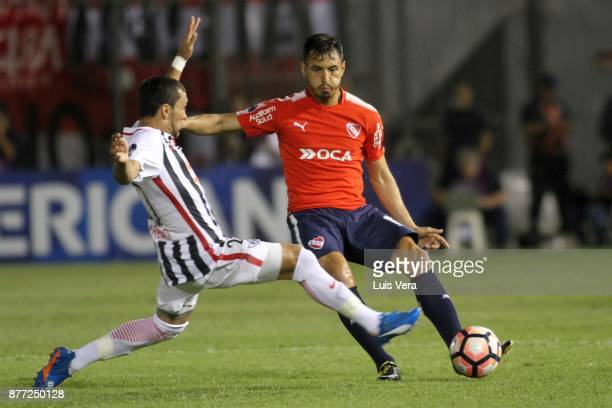 Juan Sanchez Miño of Independiente fights for the ball with Antonio Bareiro of Libertad during a first leg match between Libertad and Independiente...