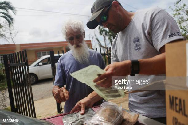 Juan Sanchez who has no electricity or running water receives instructions on how to cook an MRE from a special agent from the Special Response Team...