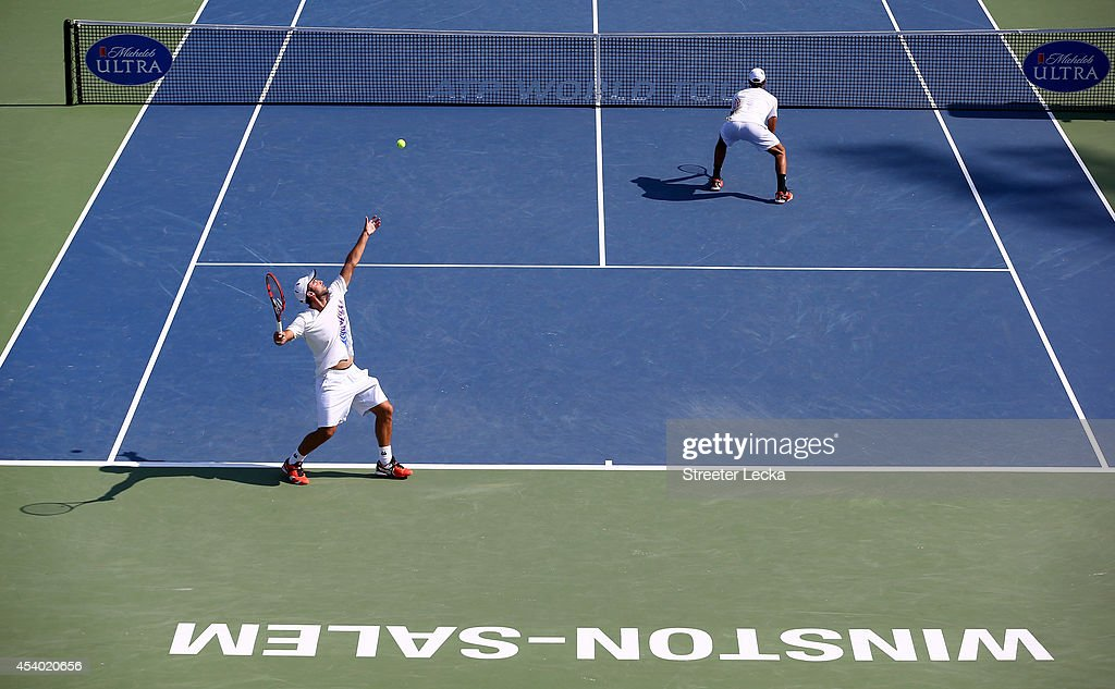 Juan Sebastian Cabal of Colombia serves with teammate Robert Farah against Jamie Murray of Great Britain and teammate John Peters of Australia during the men's doubles finals match of the Winston-Salem Open at Wake Forest University on August 23, 2014 in Winston Salem, North Carolina.
