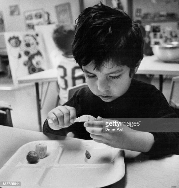 Juan Torres concentrates on cutting a strawberry for the fruit salad he and his classmates made Each youngster was given small plastic knife to work...