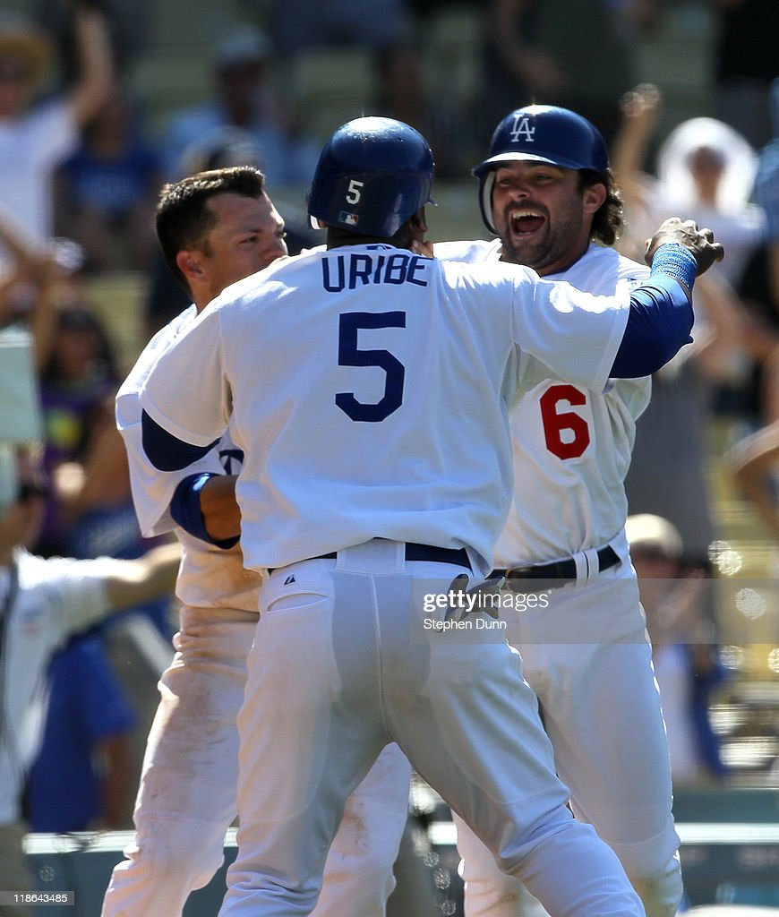 <a gi-track='captionPersonalityLinkClicked' href=/galleries/search?phrase=Juan+Uribe&family=editorial&specificpeople=209187 ng-click='$event.stopPropagation()'>Juan Uribe</a> #5 of the Los Angeles Dodgers celebrates with Aaron Miles #6 and <a gi-track='captionPersonalityLinkClicked' href=/galleries/search?phrase=Jamey+Carroll+-+Baseball+Player&family=editorial&specificpeople=211176 ng-click='$event.stopPropagation()'>Jamey Carroll</a> #14 after scoring the only run of the game with the San Diego Padres on a ninth inning two out walk off single by Dionaeer Navarro on July 9, 2011 at Dodger Stadium in Los Angeles, California. The Dodgers won 1-0.