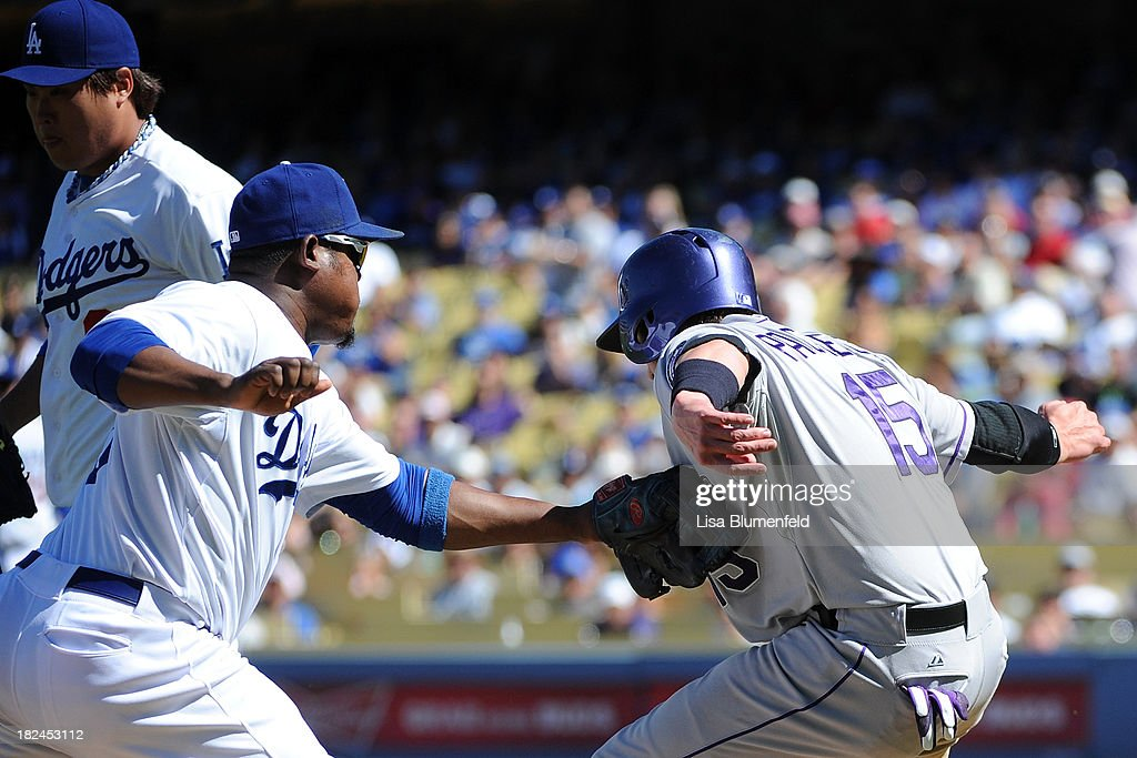 Juan Uribe #5 of the Los Angeles Dodgers tags out Jordan Pacheco #15 of the Colorado Rockies in the fourth inning at Dodger Stadium on September 29, 2013 in Los Angeles, California.