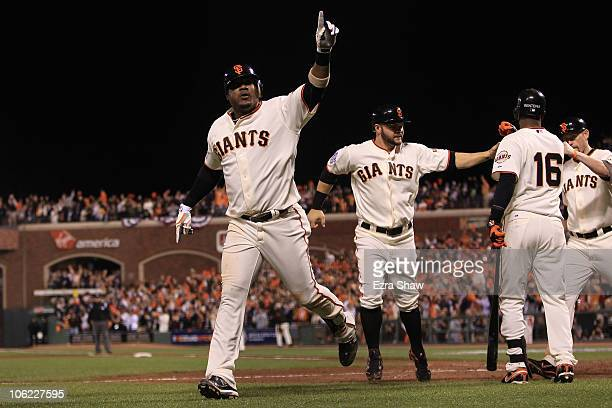 Juan Uribe of the San Francisco Giants celebrates with Cody Ross and Edgar Renteria after hitting a three run homerun in the fifth inning against...