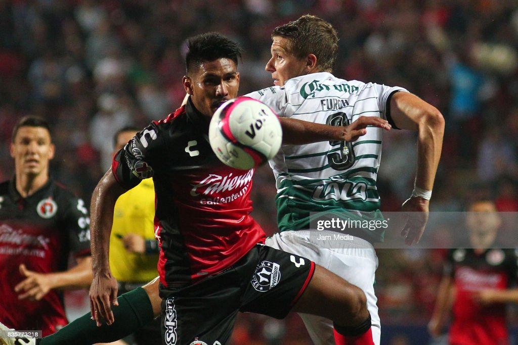 Juan Valenzuela (L) of Tijuana and Julio Furch (R) of Santos Laguna compete for the ball during the fifth round match between Tijuana and Santos Laguna as part of the Torneo Apertura 2017 Liga MX at Caliente Stadium on August 18, 2017 in Tijuana, Mexico.