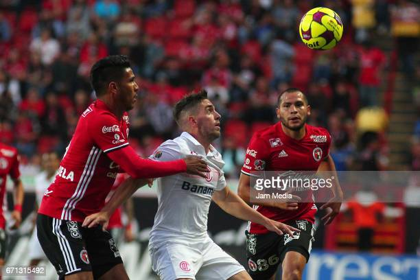 Juan Valenzuela of Tijuana Gabriel Hauche of Toluca and Carlos Vargas of Tijuana jump for the ball during the 15th round match between Tijuana and...