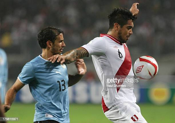 Juan Vargas of Peru fights for the ball with Cristhian Stuani of Uruguay during a match between Peru and Uruguay as part of the 15th round of the...
