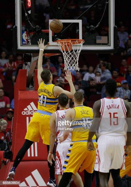 Juancho Hernangomez of the Denver Nuggets scores as Ryan Anderson of the Houston Rockets and Clint Capela and Nikola Jokic look on at Toyota Center...