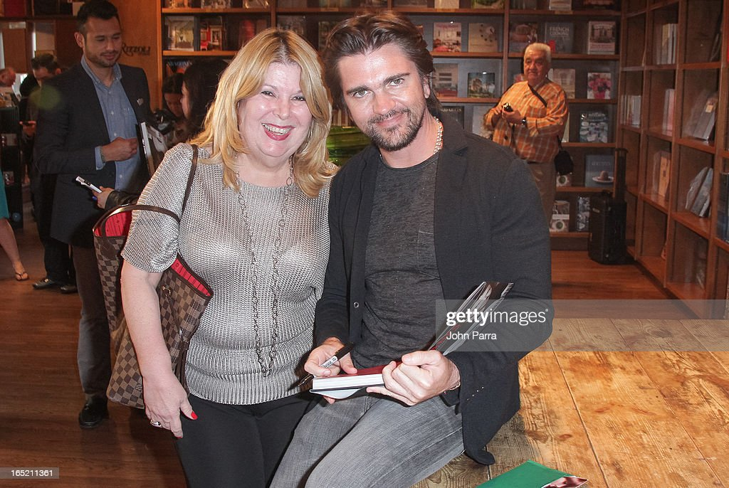 <a gi-track='captionPersonalityLinkClicked' href=/galleries/search?phrase=Juanes&family=editorial&specificpeople=202467 ng-click='$event.stopPropagation()'>Juanes</a> (R) greets fans and signs copies of his book 'Chasing The Sun' at Books and Books on April 1, 2013 in Coral Gables, Florida.