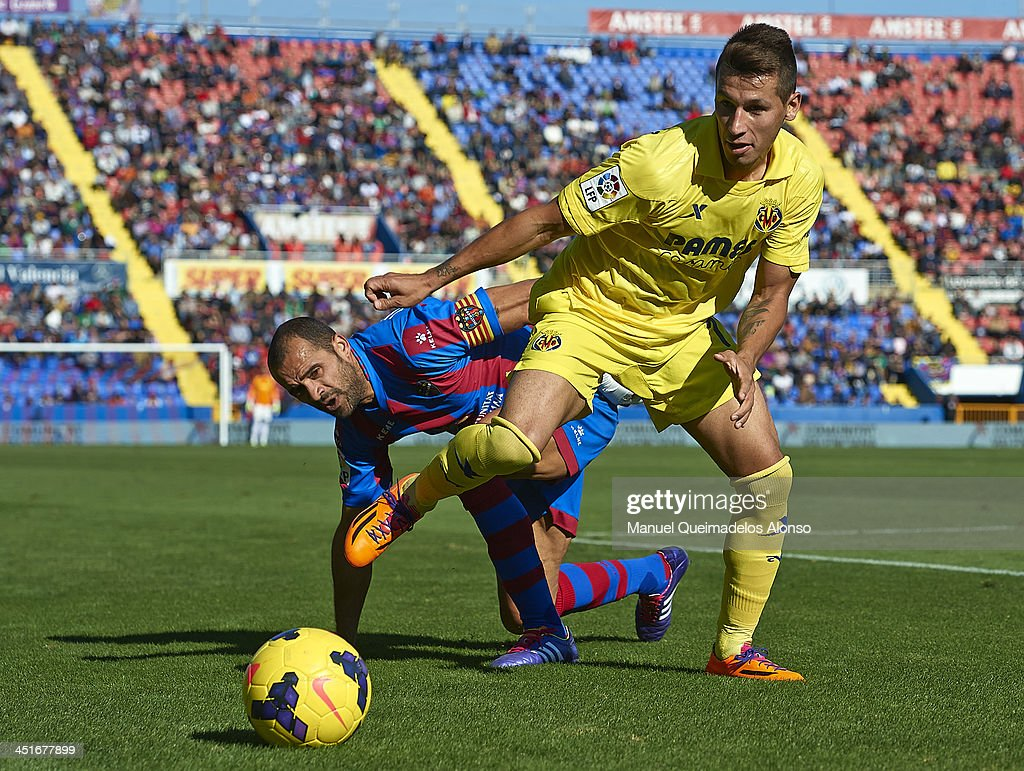 Juanfran of Levante competes for the ball ball with Hernan Perez of Villarreal during the La Liga match between Levante UD and Villarreal CF at...