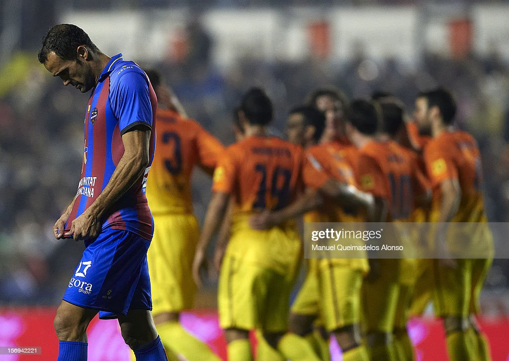 Juanfran of Levante reacts as Bacelona players celebrate during the la Liga match between Levante UD and FC Barcelona at Ciutat de Valencia on November 25, 2012 in Valencia, Spain.