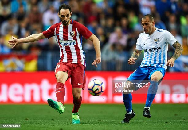 Juanfran Torres of Club Atletico de Madrid being followed by Sandro Ramirez of Malaga CF during La Liga match between Malaga CF and Club Atletico de...